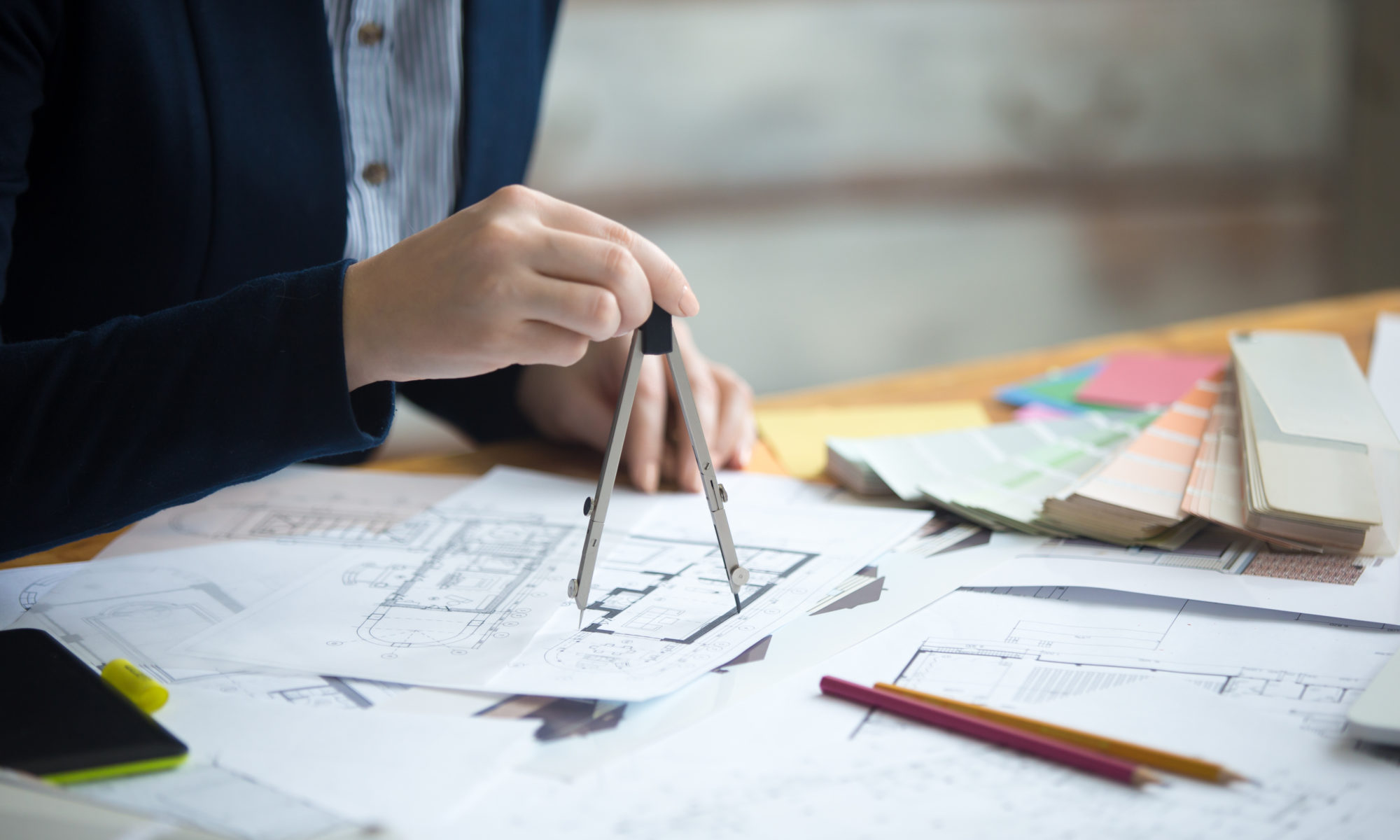 Close-up of hands of beautiful young designer person wearing suit using drawing compass on drafts. Attractive model working at office desk with blueprints for new project. Interior shot