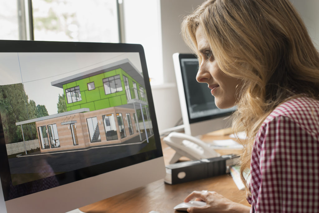 Women architect on computer looking over eco-friendly design model
