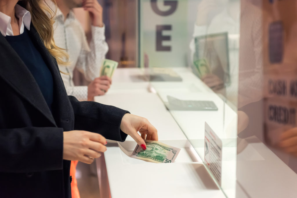 Female hand with money at cash desk inside a bank.