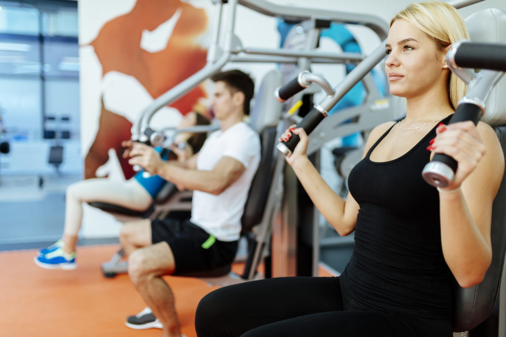 People exercising on machines in the gym