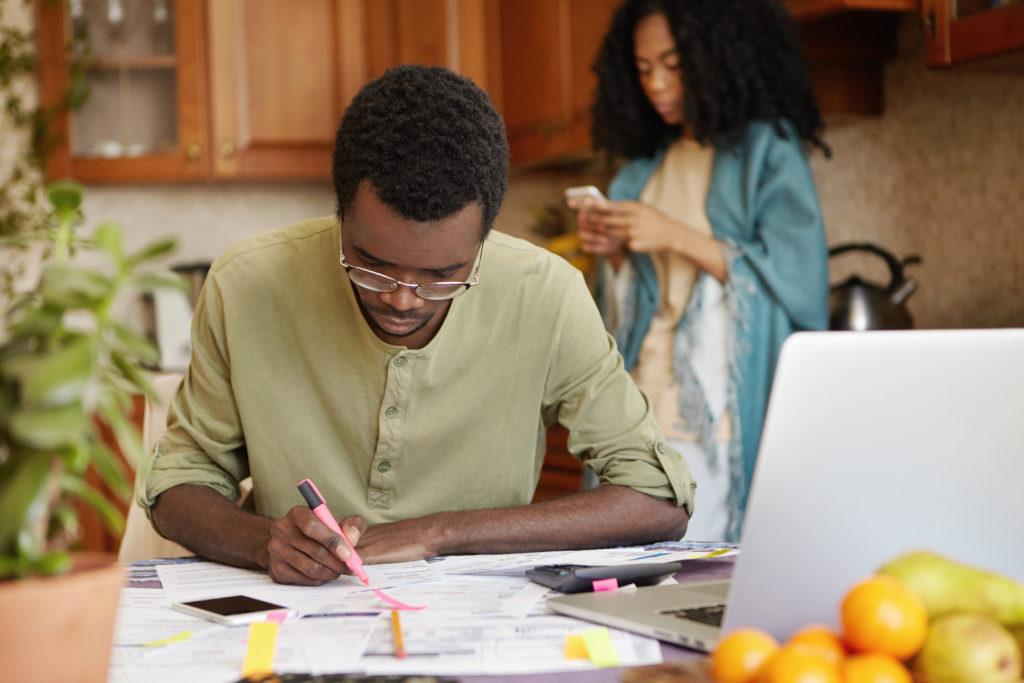 Man sitting at his kitchen table using pink felt pen, making notes on papers while planning family budget and expenses