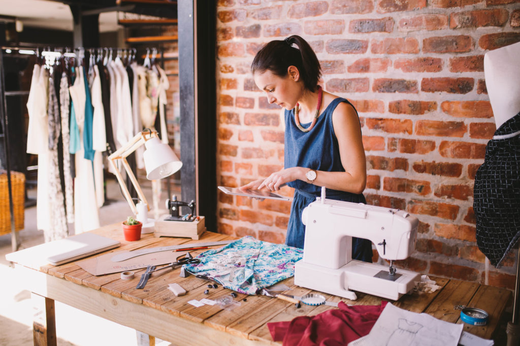 Woman in clothing shop designing and making clothing using iPad and sewing machines