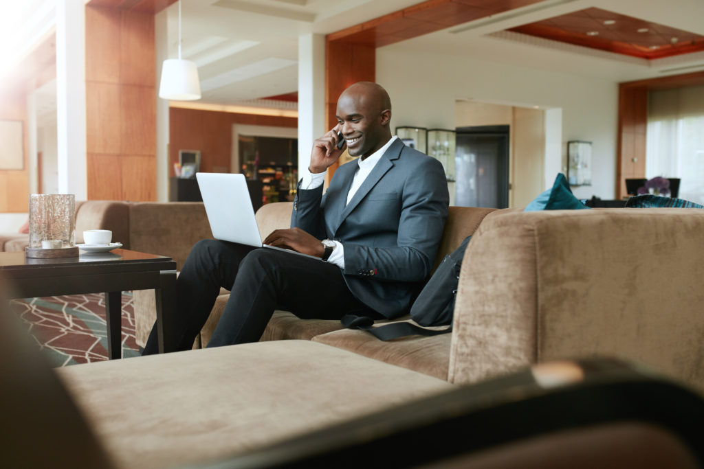 Businessman in hotel lobby sitting on a coach using cell phone and laptop