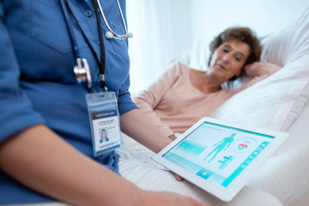 Doctor holding a digital tablet looking at medical records and test results while she treats an elderly female patient