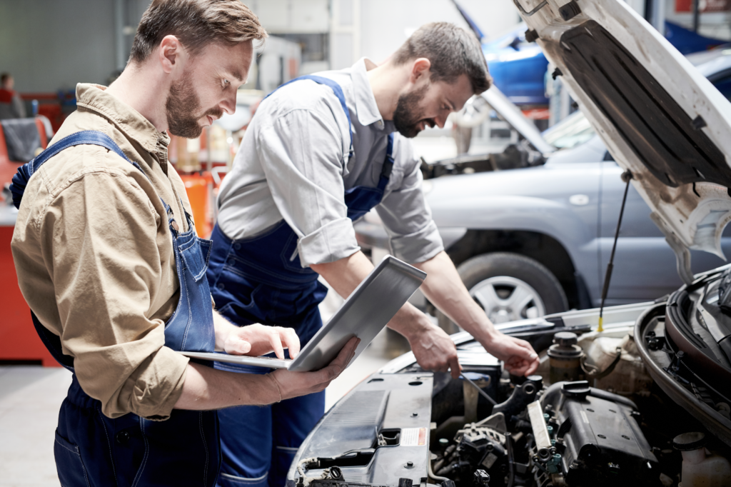 Two Male Mechanics Working on a Car in the Car Service Garage