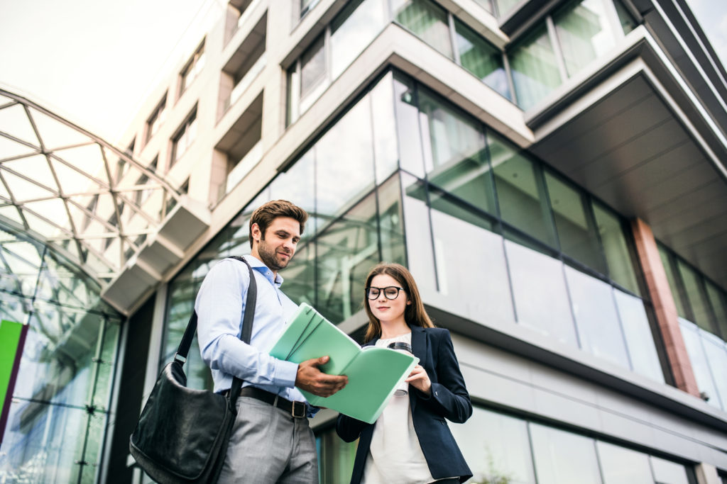 A young businessman and businesswoman standing in front of a commercial building, looking at notes and talking.
