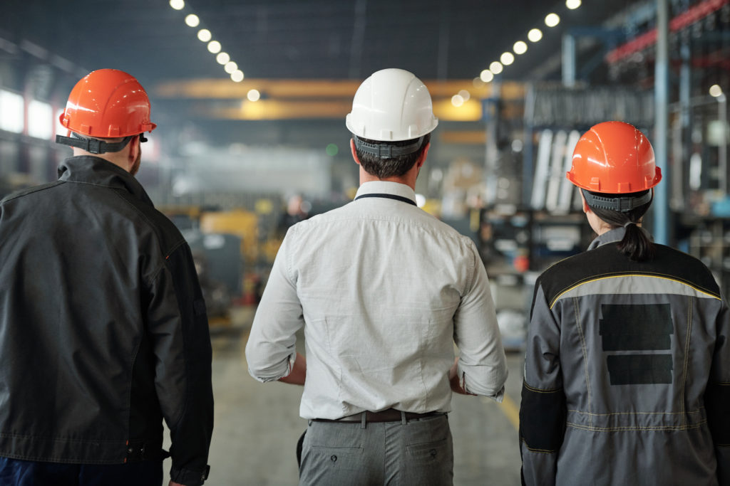 Rear view of engineers in work helmets standing in contemporary workshop and examining manufacturing processes together