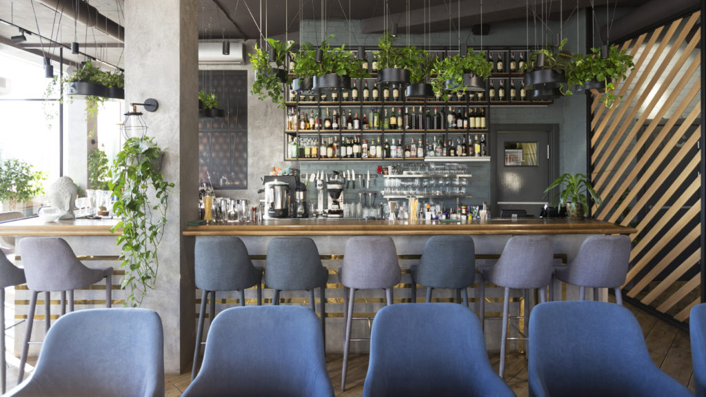 Modern restaurant with a wooden counter-top bar surrounded by green plants and modern decor